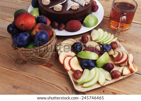 whole big chocolate cream brownie cake topped with white chocolate and cream flowers with hot tea cup decorated with fruits apple plum and grape on plate on wooden table - stock photo