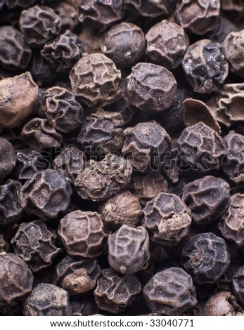 Whole black pepper corns macro shot, toned - stock photo