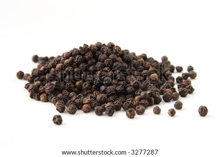 Whole black pepper, isolated on white. Shallow depth of field, focused on the centre of the pile. - stock photo