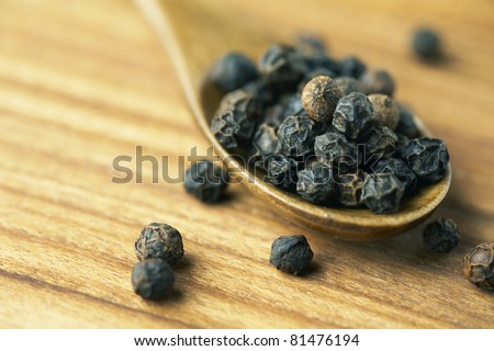 Whole black pepper on wooden spoon. - stock photo