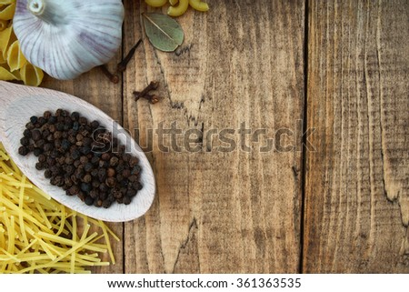 Whole black pepper on wooden spoon, pasta and garlic
