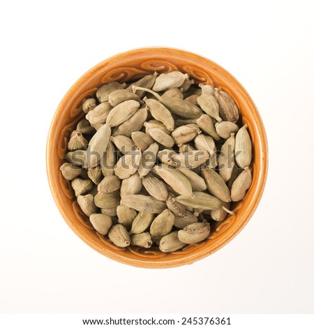 Whole Cardamom seeds in orange bowl, isolated on white - stock photo