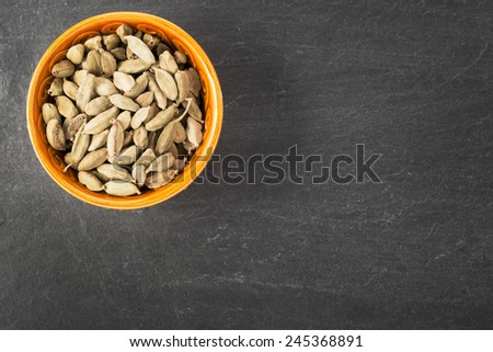 Whole Cardamom seeds in orange bowl on grey stone surface with copy space. - stock photo