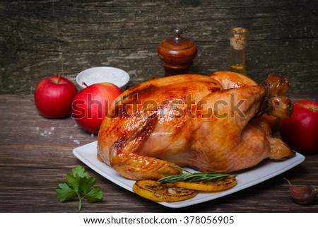 whole chicken noticed roasted with lemon and apples on a plate on a wooden background.