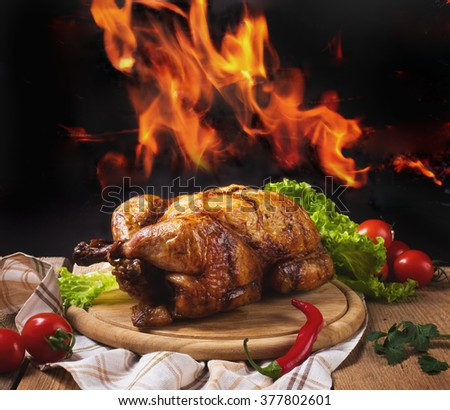 Whole chicken on background of flames - stock photo