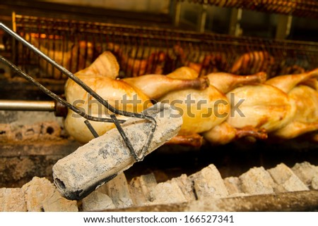 Whole chicken roasting over coals - stock photo