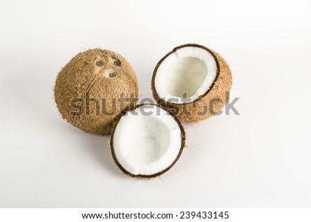 Whole Coconut and cracked sections with kernel on a white background