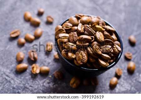 Whole coffee beans in a cup on a dark surface. Selective focus. - stock photo