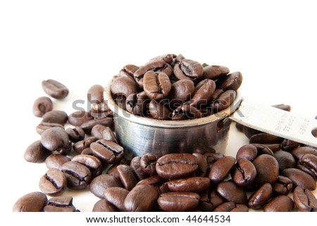 Whole coffee beans spilling out of a full coffee measure. Shot on white background. Focus is on the edge of the cup. Beans in the foreground are out of focus. - stock photo