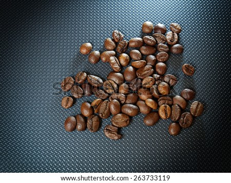 Whole coffee grains on a gray background. - stock photo