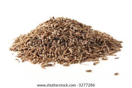 whole cumin seeds, isolated on white. Shallow depth of field, focused on the centre of the pile. - stock photo