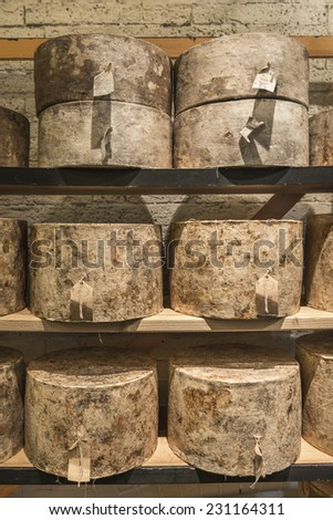 Whole cylindrical  cheese truckles maturing on shelves - stock photo