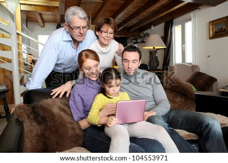 Whole family around a laptop - stock photo