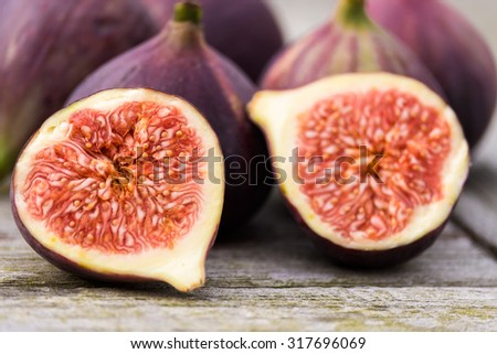 Whole figs and one fig sliced in half on top of a teak garden table. Focus is on the sliced fig. - stock photo