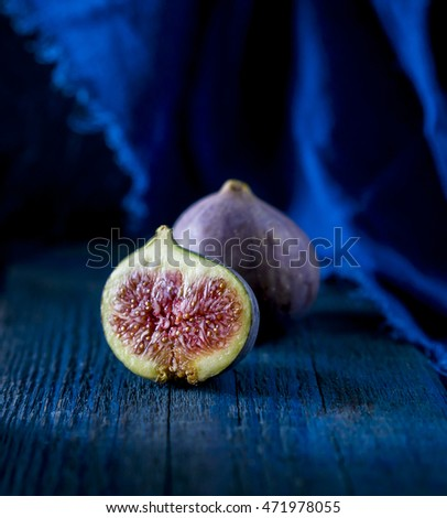 Whole figs and one fig sliced  on top of wooden table. Focus is on the sliced fig