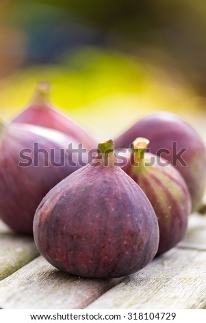 Whole figs on top of a teak garden table. Focus is on the front fig. - stock photo