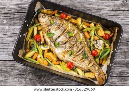 whole fish baked in a baking dish with potatoes, cherry tomatoes, green beans, lemon, baby carrots and basil on an old table, top view, horizontal - stock photo