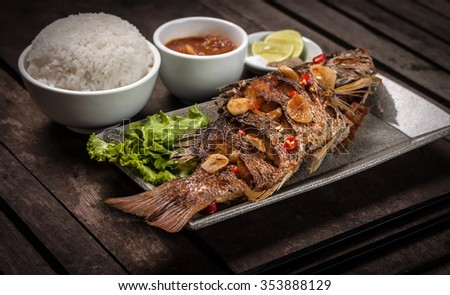 Whole fish fried served with rice, red sauce and seasoning - stock photo