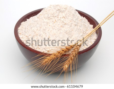 Whole flour in bowl with wheat ears on white background - stock photo