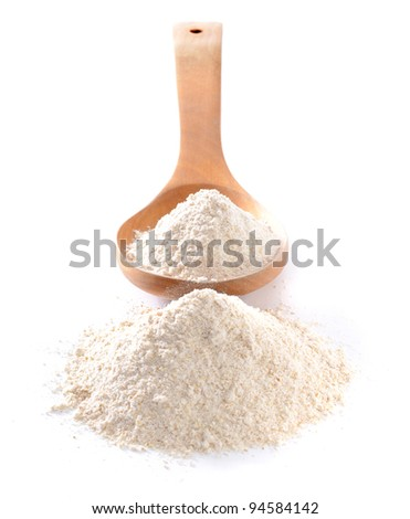 Whole flour in spoon on white background with shallow depth of field - stock photo
