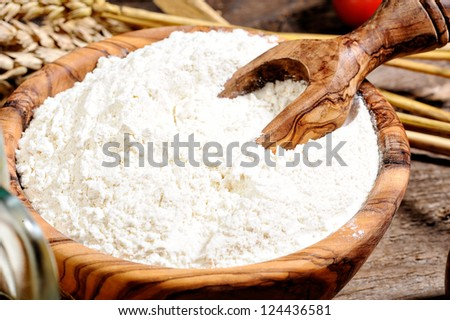 Whole flour in wooden bow on a wood background - stock photo