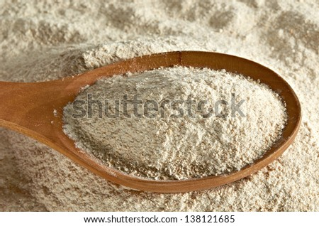 Whole flour in wooden spoon - stock photo