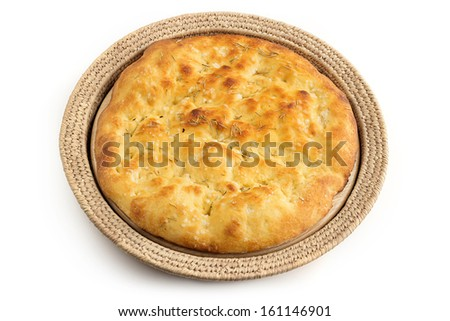 whole focaccia in a straw tray over white