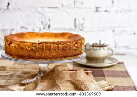 Whole fresh creamy traditional cheesecake on a glass plate with cup of coffee on the white brick wall - stock photo