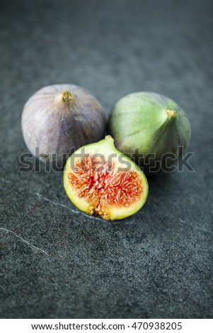 Whole fresh figs and one slice of figs. Focus is on the sliced fig