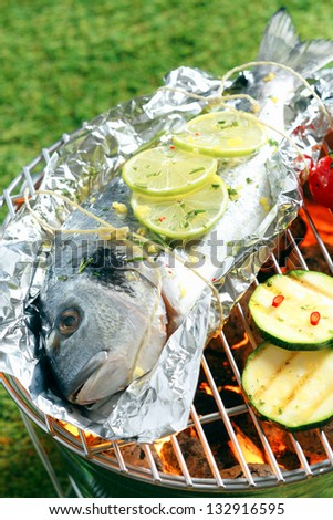 Whole fresh gilthead breem garnished with sliced lemon roasting on aluminium foil over the glowing coals in a barbecue - stock photo