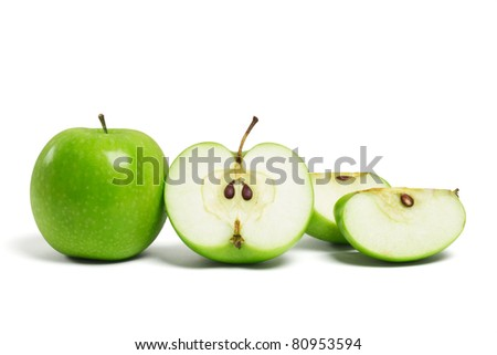 Whole fresh green apple and sliced pieces on white background - stock photo