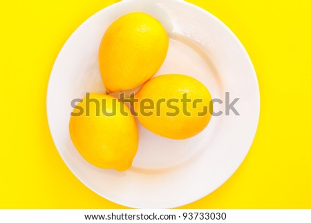 Whole fresh lemons on a white plate against a yellow background.  Overhead, top view - stock photo