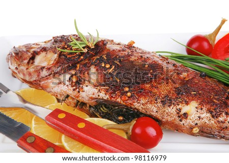 whole fried bass on plate, served with lemons and tomatoes isolated on white - stock photo
