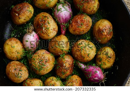 Whole fried  potato and onion topped with spices and chopped dill in cast iron pan - stock photo