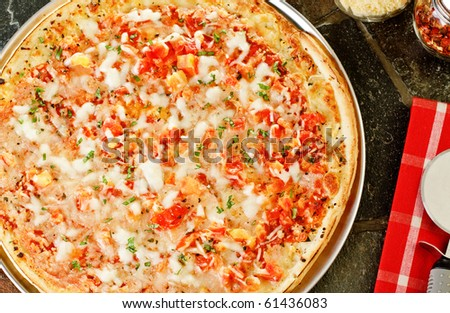 Whole Frozen pizza with cutter and napkin