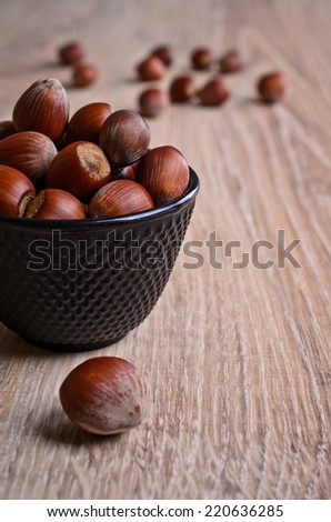 Whole fruit hazelnut lie in a pot of black which stands on a wooden surface