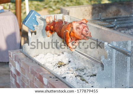 Whole glazed spit roast pig cooking on an outdoor BBQ on a garden patio for dinner for a festive occasion - stock photo
