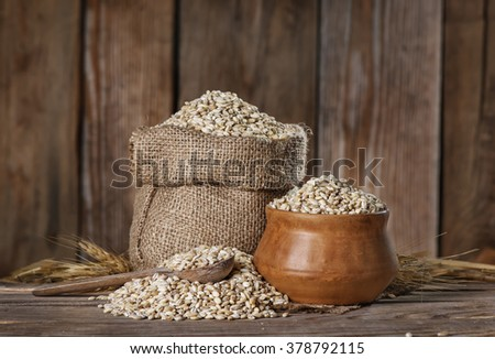 whole grain barley in the bag and in a clay bowl, bunch of whole barley grains on an old wooden background - stock photo