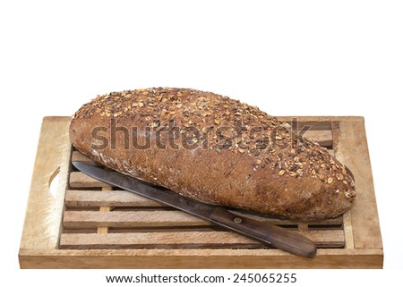 Whole Grain Bread and Vintage Knife on Wooden Cutting Board over white background - stock photo