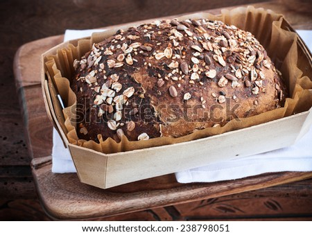 Whole grain bread on cutting board - stock photo