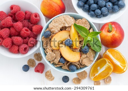 whole-grain flakes with fresh fruit and berries, close-up, top view, horizontal - stock photo
