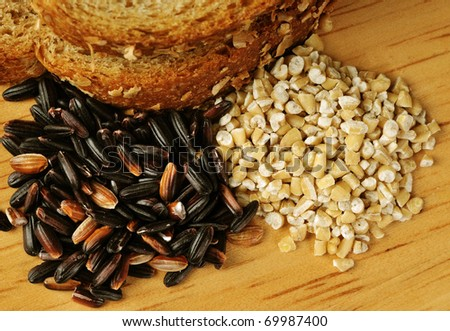 Whole grain goodness.  Close up image of whole wheat bread, steel cut oats, and black (mahogany) rice on wood cutting board. - stock photo
