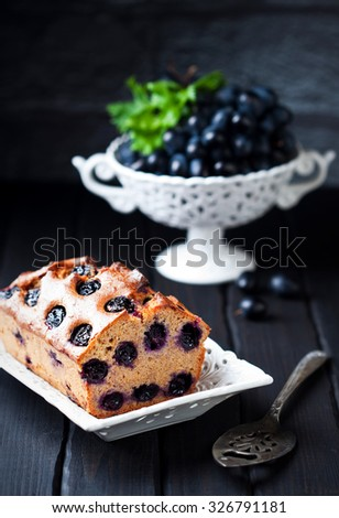 Whole grain loaf cake with grapes, selective focus - stock photo