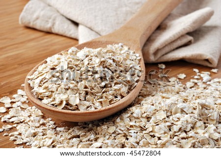 Whole grain, rolled oats with wooden spoon and homespun napkin.  Macro with extremely shallow dof. - stock photo