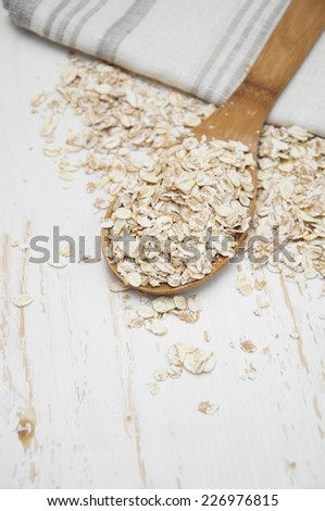 Whole grain, rolled oats with wooden spoon and napkin - stock photo
