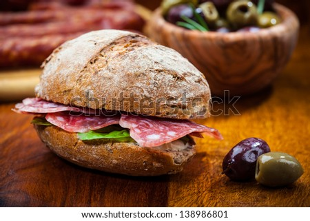 Whole grain sandwich with Italian salami, goat cheese and fresh olives - stock photo
