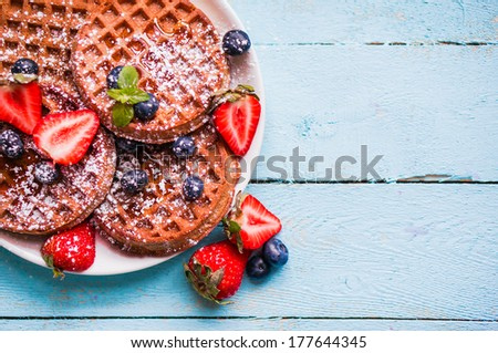 Whole grain waffles with berries on blue wooden background - stock photo