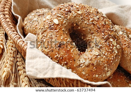 Whole grain wheat bagel in basket with wheat spikes and oats.  Macro with shallow dof. - stock photo