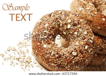 Whole grain wheat bagels with oat flakes on white background with copy space.  Macro with shallow dof. - stock photo
