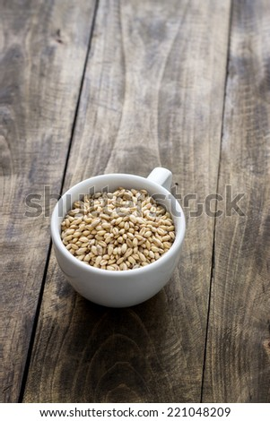 whole grain wheat in a cup over rustic wooden background - stock photo